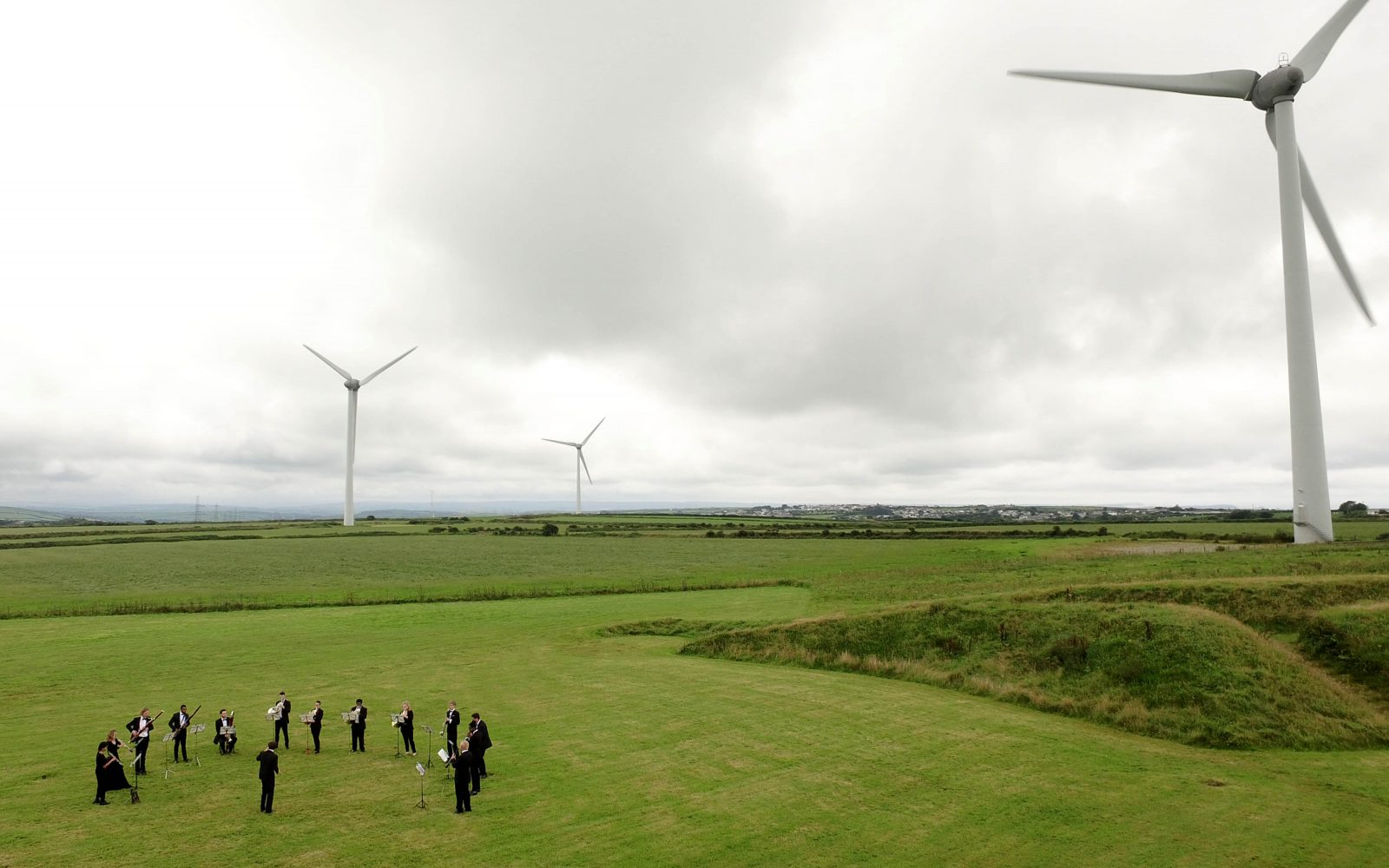 The Orchestra for the Earth performs by wind turbines at Delabole wind farm. Image: Emily Whitfield-Wicks.